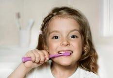De schoonmakende tanden van het kindmeisje met tandenborstel Royalty-vrije Stock Afbeeldingen