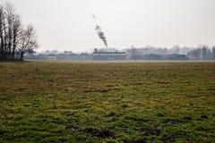 de schoorsteen van een fabriek verdrijft dampen in het platteland royalty-vrije stock fotografie