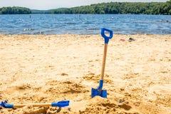 De schop van het jonge geitjeshulpmiddel op de zijachtergrond van het strandmeer stock fotografie