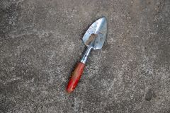 De schop van het tuinhulpmiddel met rood handvat in hand op houten muurachtergrond stock foto