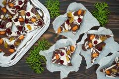De schors van de vakantiechocolade met droge vruchten en noten op een donkere houten achtergrond Hoogste mening Dessertrecept voo Royalty-vrije Stock Afbeelding
