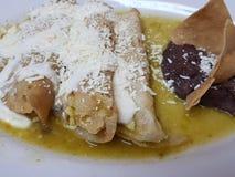 de schotel met groene enchiladas en refried bonen, typisch Mexicaans voedsel stock fotografie