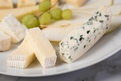 De schotel van de kaasplaat met selectie Edamer, Parmezaanse kaas, geit, blauw en roomkaas, edele en druiven op marmeren achtergr royalty-vrije stock fotografie