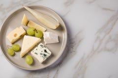 De schotel van de kaasplaat met selectie Edamer, Parmezaanse kaas, geit, blauw en roomkaas, edele en druiven op marmeren achtergr stock foto's