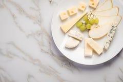 De schotel van de kaasplaat met selectie Edamer, Parmezaanse kaas, geit, blauw en roomkaas, edele en druiven op marmeren achtergr stock afbeeldingen