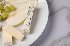 De schotel van de kaasplaat met selectie Edamer, Parmezaanse kaas, geit, blauw en roomkaas, edele en druiven op marmeren achtergr stock afbeelding