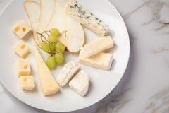 De schotel van de kaasplaat met selectie Edamer, Parmezaanse kaas, geit, blauw en roomkaas, edele en druiven op marmeren achtergr royalty-vrije stock foto's