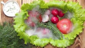 De schotel is verfraaid met sla is tomaten, komkommer en radijzen met dille die in ochtendmist wordt behandeld Lichte bl van de o stock footage