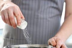 De Schotel Wit Overzees van chef-kokwearing apron adding Zout royalty-vrije stock fotografie