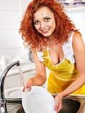 De schotels van de vrouwenwas bij keuken. Stock Foto's