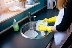 De schotels van de vrouwenwas in de keuken met spons royalty-vrije stock foto