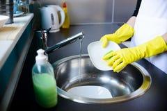 De schotels van de vrouwenwas in de keuken met spons stock fotografie