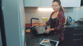 De schotels van de meisjeswas in de keuken scherpe raad Vrouwenkoks in de keuken het meisje wast een mes in de gootsteen stock videobeelden