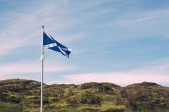 De Schotse vlaggolven in de wind met typisch hoogland scener stock afbeelding