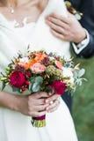 De schouder van de bruidegomholding van bruid met rood roze boeket in handen Stock Afbeeldingen