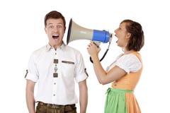 De schreeuwen van de vrouw in oor van de mens met megafoon Stock Afbeeldingen