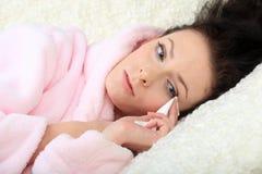 De schreeuwende jonge vrouw ligt op een bank en veegt weg scheuren af Stock Foto's
