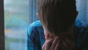 De schreeuwende jongen kijkt uit het venster in de regen stock video