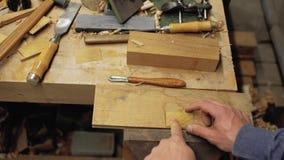 De schrijnwerker neemt houten baardkam in houten patroon op handmade 4K stock videobeelden