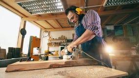 De schrijnwerker poetste hout op terwijl het werken bij een timmerwerkwinkel Timmerman, vakman het werken stock videobeelden
