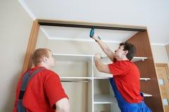 De schrijnwerkers van de garderobe bij installatie werken Stock Foto