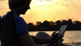 De schrijver Sits op een Vouwende Stoel en bekijkt Zijn Tabletpc bij Zonsondergang stock footage