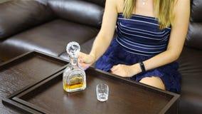De schuchtere vrouw onderzoekt en raakt de karaf met alcohol stock videobeelden