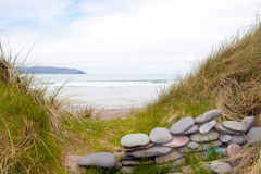 De schuilplaats van de steenmuur op een mooi Iers strand Stock Foto