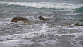 De schuimende golf van de Zwarte Zee accumuleert op een rots op het zandige strand van het dorp van Novy Svet in de Krim niemand stock videobeelden