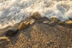 De schuimende overzeese kust bij het strand, sluit omhoog Royalty-vrije Stock Afbeeldingen