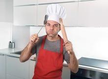 De schuimspaan en de deegrol van de mensenholding in schort en de keuken van de kokhoed thuis Royalty-vrije Stock Foto's