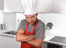 De schuimspaan en de deegrol van de mensenholding in schort en de keuken van de kokhoed thuis Stock Foto's