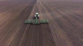 De schuine stand schoot: De tractor trekt een landbouwapparaat voor harrowing het land Het de lentewerk op het gebied, luchtvideo stock videobeelden