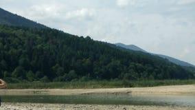De schuine stand schoot van heuvels aan vrouwenzitting als picknickvoorzitter naast een rivier stock footage