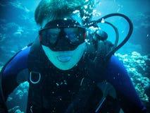 De scuba-duiker is onderwater met volledig materiaal Hij gekscheert tonend tong Royalty-vrije Stock Afbeelding