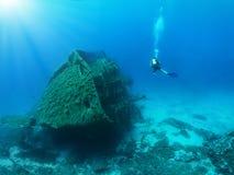 De scuba-duiker onderzoekt een gedaald wrak royalty-vrije stock afbeelding