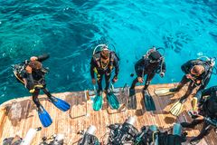 De scuba-duiker zit op het jacht en klaar te duiken royalty-vrije stock afbeelding