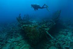 De scuba-duiker zwemt over zeer oud schipwrak royalty-vrije stock foto's