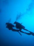 De scuba-duikers silhouetteren royalty-vrije stock afbeeldingen