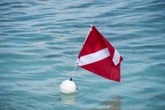 De scuba-uitrusting duikt boei met vlag in tropisch water royalty-vrije stock foto's