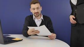 De secretaresse brengt de documenten aan de werkgever stock videobeelden