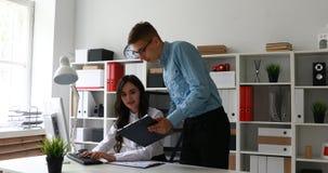De secretaresse drukt tekst op computer en het ontvangen van instructies van directeur stock footage