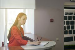 De secretaresse in een rood kostuum zet een zegel in de inkomende berichten het bureauwerk, documentcontrole royalty-vrije stock foto's