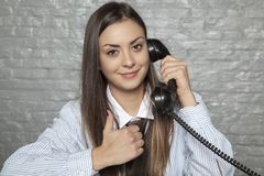 De secretaresse spreekt op de telefoon, toont de duim stock foto's