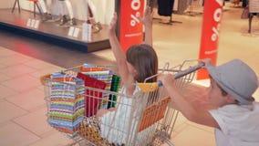De seizoengebonden verkoop, vrolijke kinderenrit koopt karretjes bij winkelcentrum voorbij winkelvensters van in boutique stock video