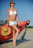 De seksuele jonge blondevrouw met het mooie lichaam stellen op een strand in een wit badpak tegen de oceaan Royalty-vrije Stock Foto