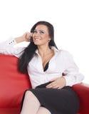 De seksuele telefoon en de glimlach van de vrouwenvraag op rode bank Stock Foto