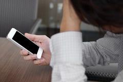 De selectieve nadruk op mobiele slimme telefoon wordt gehouden met handen van de beklemtoonde jonge mens in bureau stock afbeelding