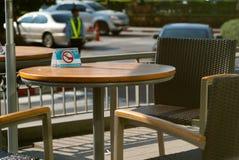 De selectieve nadruk op non-smoking teken op de houten uitstekende lijst en vacaturestoelen bij het terras van koffie winkelt in  royalty-vrije stock foto's