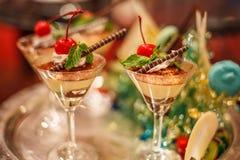 De selectieve nadruk van Chocolade romige kleinigheid in mooie cocktailglazen met vers rood rijp kersenfruit en de chocolade bewe stock foto